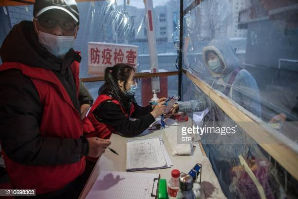 This photo taken on April 22 2020 shows a staff member checking the body temperature of a woman before she enters a community in the border city of...