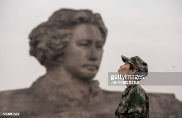 This photo taken on April 22 shows soldiers of the People's Liberation Army pose for pictures in front of a 32meter statue of late Chairman Mao...
