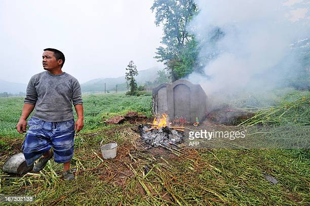 This photo taken on April 23 2013 shows a man giving offerings before a grave sit in Lushan county of Yaan southwest China's Sichuan province Tens of...