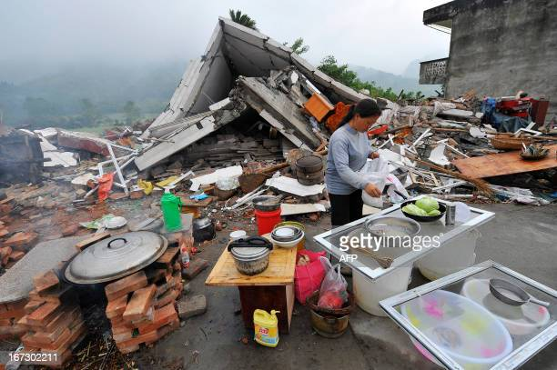 This photo taken on April 23 2013 shows a woman cooking beside collapsed houses in Lushan county of Yaan southwest China's Sichuan province Tens of...