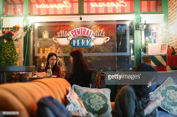 """This photo taken on April 23, 2018 shows customers talking at the """"Central Perk"""" coffee shop in Shanghai. - Millions of Chinese """"Friends"""" fans are..."""