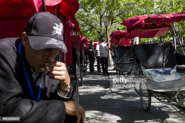 TOPSHOT This photo taken on April 24 2017 shows rickshaw drivers waiting for customers in a touristic area in Beijing Appearing in China at the end...
