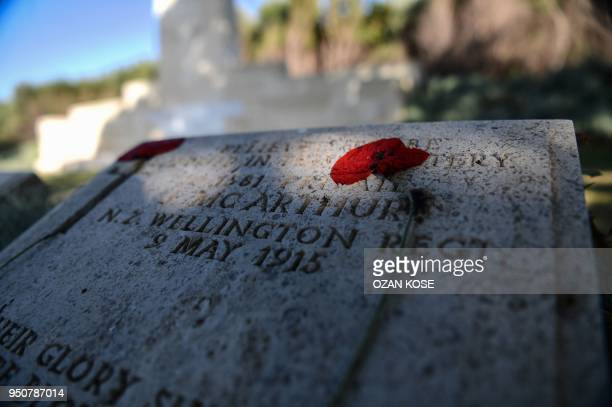 This photo taken on April 24 2018 shows a dried poppy flower placed on a soldier's gravestone at the ANZAC cemetery in Canakkale on April 24 on the...