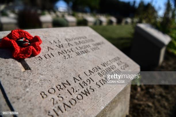 TOPSHOT This photo taken on April 24 2018 shows a handmade poppy flower placed on a soldier's gravestone at the ANZAC cemetery in Canakkale on April...