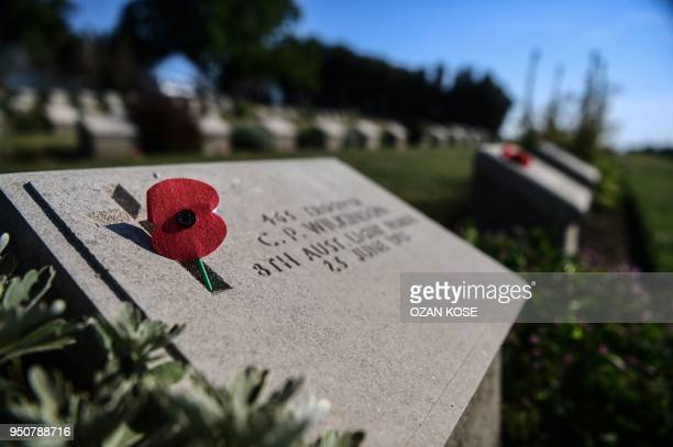 This photo taken on April 24 2018 shows a handmade poppy flower placed on a soldier's gravestone at the ANZAC cemetery in Canakkale on April 24 on...
