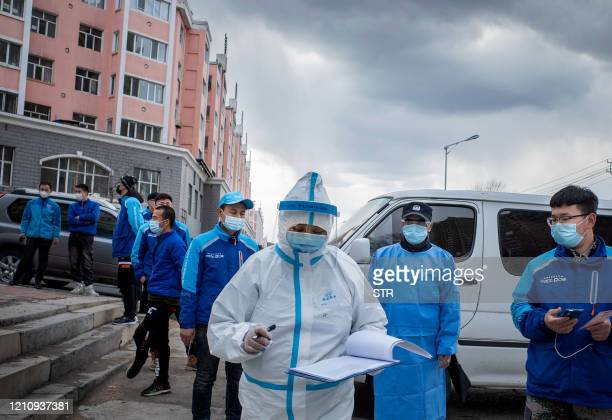 This photo taken on April 24 shows a medical worker checking notes in front of food delivery employees in queue to have their nucleic acid test as...