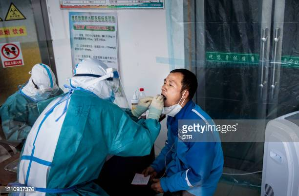 This photo taken on April 24 shows medical personnel taking swab samples of a man for nucleic acid testing as part of COVID19 pandemic measures at a...