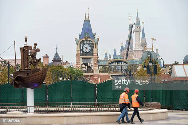 This photo taken on April 25 2016 shows workers walking past the new Shanghai Disney Resort in the Pudong area of Shanghai The Disney resort station...