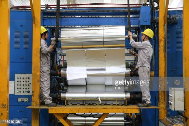 This photo taken on April 25, 2019 shows workers rolling sheet aluminium at a factory in Huaibei in China's eastern Anhui province. / China OUT