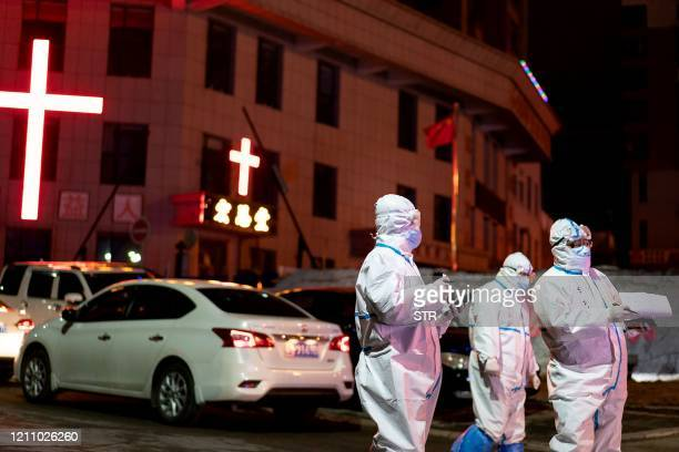 This photo taken on April 25 2020 shows medical workers wearing protective gear looking for close contacts with patients that tested positive on...