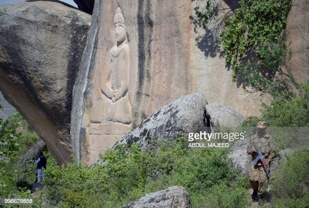 This photo taken on April 26 2018 shows a Pakistani soldier walking past the seventhcentury rock sculpture of a seated Buddha carved into a mountain...