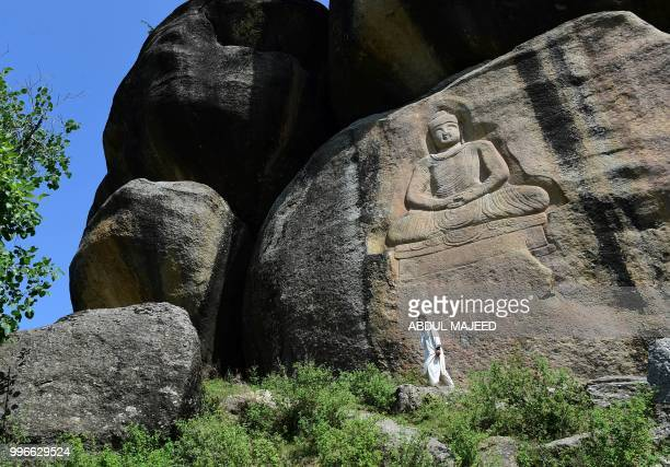 This photo taken on April 26 2018 shows a Pakistani visitor walking past a seventhcentury rock sculpture of a seated Buddha carved into a mountain in...