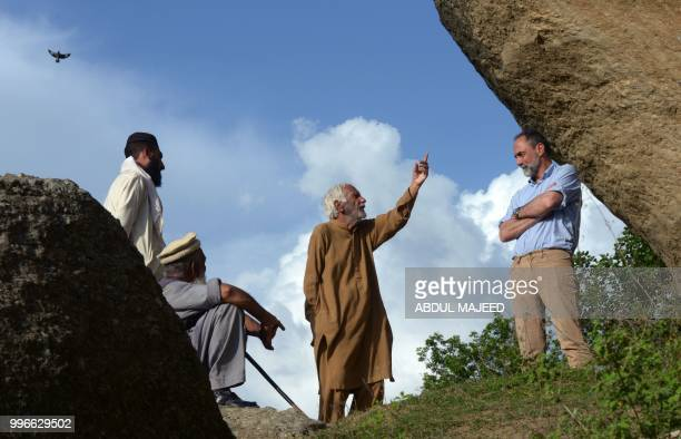 This photo taken on April 26 2018 shows Italian archaeologist Luca Maria Olivieri speaking with Pakistani historian Parvesh Shaheen next to the...