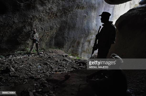 This photo taken on April 26 2018 shows Pakistani soldiers standing guard at the site of the seventhcentury rock sculpture of a seated Buddha carved...