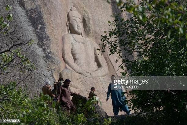 This photo taken on April 26 2018 shows Pakistani visitors walking past the seventhcentury rock sculpture of a seated Buddha carved into a mountain...
