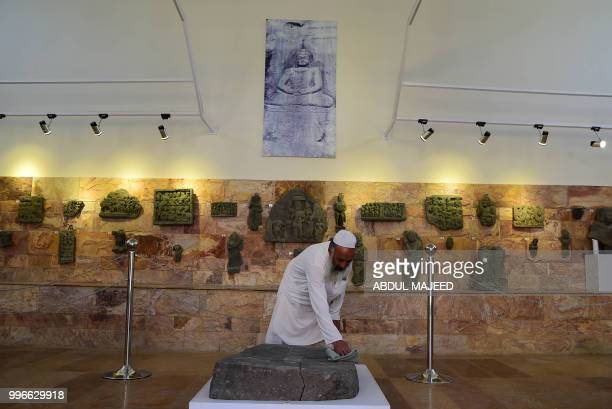 This photo taken on April 27 2018 shows a worker cleaning a rock with images of Buddha's feet at a museum in the town of Mingora the capital of...