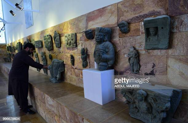 This photo taken on April 27 2018 shows a worker cleaning statues of Buddha at a museum in the town of Mingora the capital of northwestern Swat...
