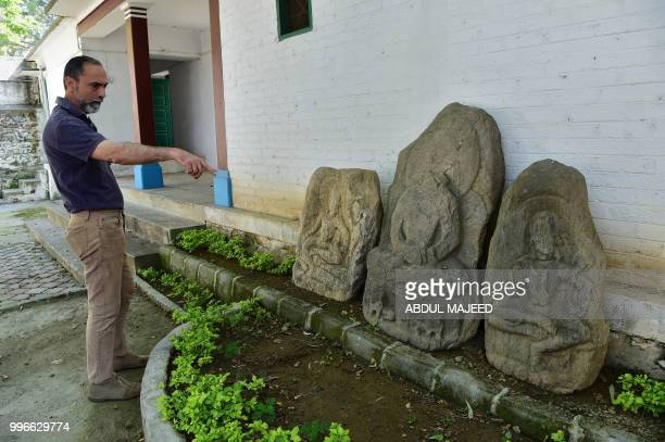This photo taken on April 27 2018 shows Italian archaeologist Luca Maria Olivieri pointing towards Buddhist statues at an archaeological site in the...