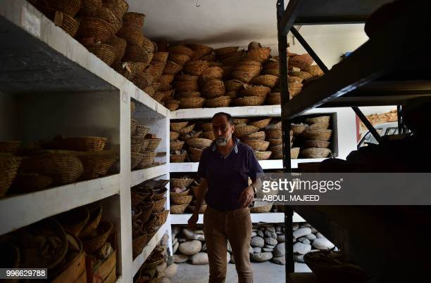 This photo taken on April 27 2018 shows Italian archaeologist Luca Maria Olivieri walking by the remains of the destroyed Buddha in the town of...