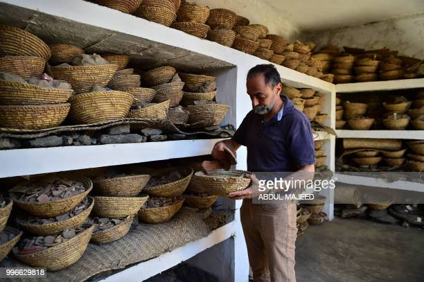 This photo taken on April 27 2018 shows Italian archaeologist Luca Maria Olivieri looking through the remains of the destroyed Buddha in the town of...