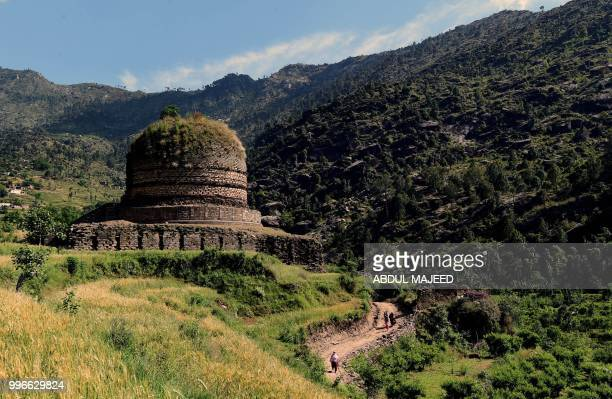 This photo taken on April 27 2018 shows Pakistani visitors walking past a centuriesold stupa a domeshaped Buddhist monument in the town of Amluk Dara...