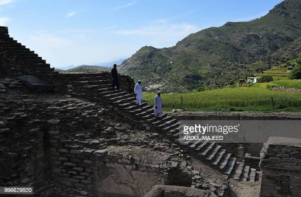 This photo taken on April 27 2018 shows Pakistani visitors walking down stairs to see a centuriesold stupa a domeshaped Buddhist monument in the town...
