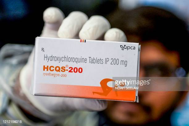 This photo taken on April 28 2020 shows a pharmacist displaying a box of hydroxychloroquine tablets in his store in Hyderabad India has ramped up...