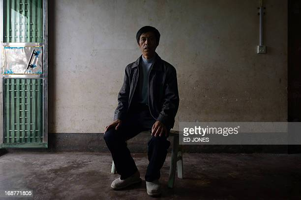 This photo taken on April 29, 2013 shows former construction worker Cao Jieshi who suffers from black lung disease, posing at his home in the village...