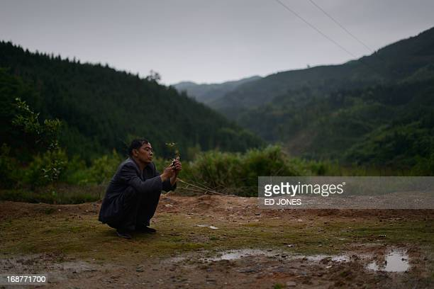 This photo taken on April 29, 2013 shows former construction worker Xu Zhihui who suffers from black lung disease, making a phone call outside the...