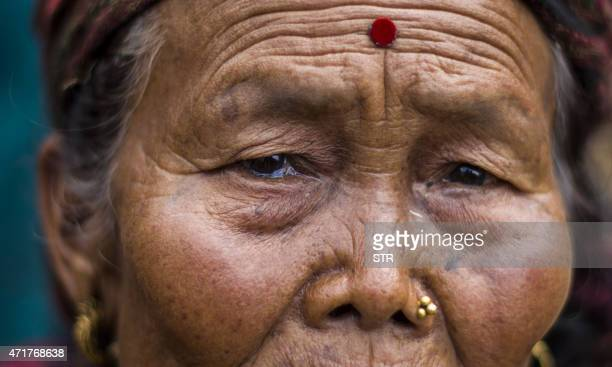 This photo taken on April 30 2015 shows an elderly lady holding her tears in Paslang village in Gorkha Nepal Desperate survivors living at ground...