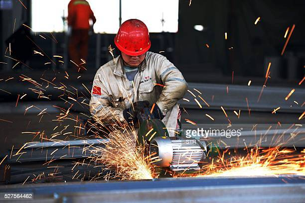 This photo taken on April 30 2016 shows a worker polishing a piece of work at a structural steelworks company in Rizhao in eastern China's Shandong...