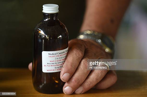 This photo taken on April 30 2016 shows Aboriginal Australian Tony Bower holding a bottle of medical cannabis in oil form as he talks to AFP at his...