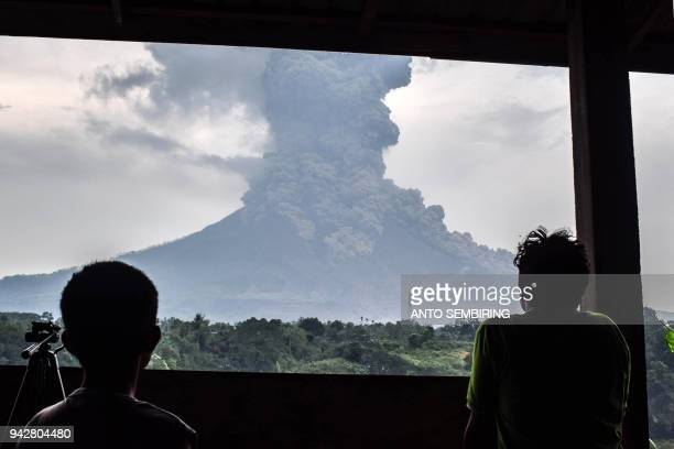 This photo taken on April 6 2018 shows villagers watching from the town of Karo as Mount Sinabung volcano spews thick volcanic ash Sinabung roared...