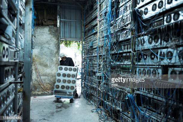 This photo taken on April 6, 2021 shows a local resident working part time at a cryptocurrency farm in Dujiangyan in China's southwestern Sichuan...