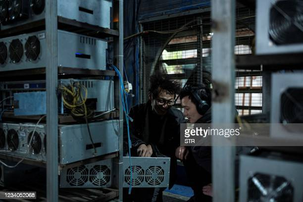 This photo taken on April 6, 2021 shows two workers chatting at a cryptocurrency farm in Dujiangyan in China's southwestern Sichuan province. - China...