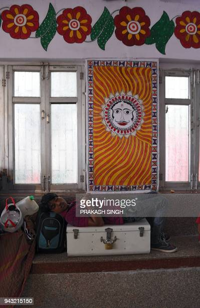 This photo taken on April 7 shows an Indian man takaking a nap in a waiting room painted with Mithila or Madhubani paintings at Madhubani railway...