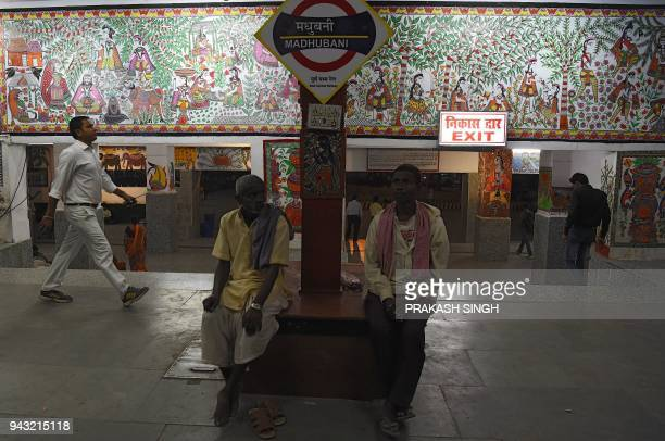 This photo taken on April 7 shows Indian passengers waiting for train in a area decorated with Mithila or Madhubani paintings at Madhubani railway...