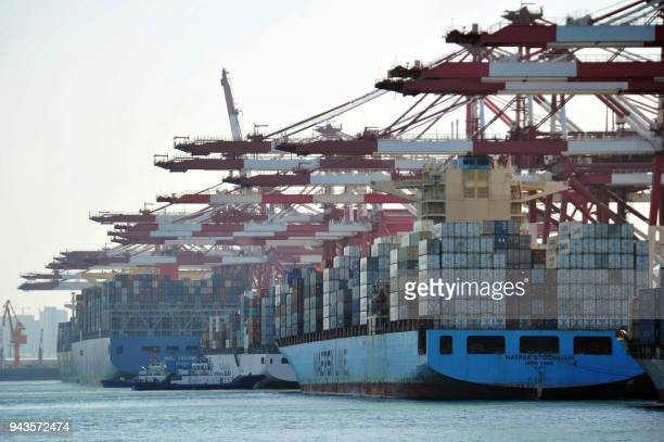 This photo taken on April 8 2018 shows cargo containers loaded on container ships at a port in Qingdao in China's eastern Shandong province China...