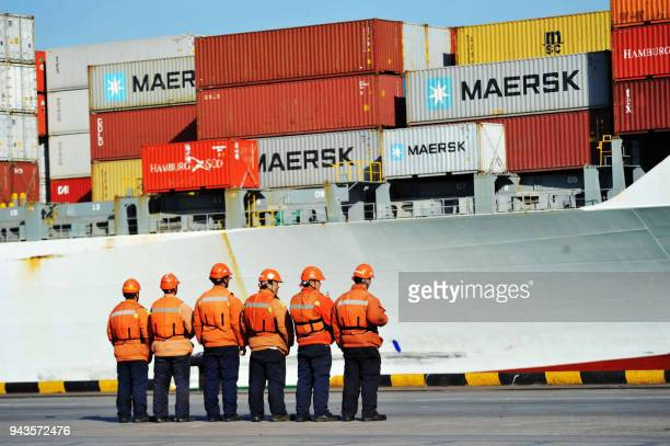 This photo taken on April 8 2018 shows workers stand in line next to a container ship at a port in Qingdao in China's eastern Shandong province China...
