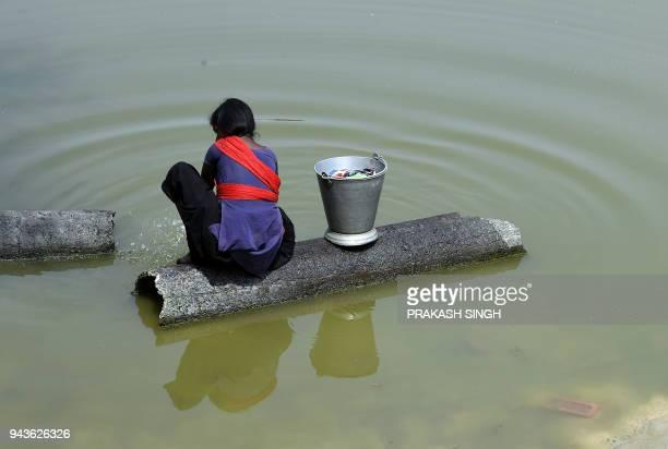TOPSHOT This photo taken on April 8 shows an Indian girl washing clothes in a pond at Sarisabpahi Village in Madhubani district in Bihar