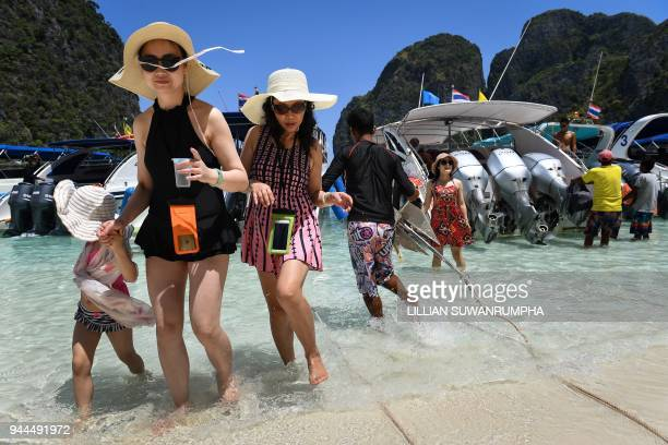 This photo taken on April 9 2018 shows tourists getting off a speedboat onto Maya Bay on the southern Thai island of Koh Phi Phi Across the region...
