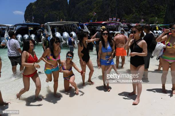 This photo taken on April 9 2018 shows tourists in front of a row of speedboats in Maya Bay on the southern Thai island of Koh Phi Phi Across the...
