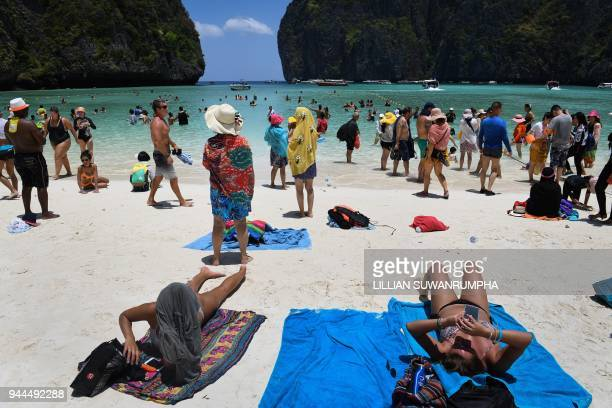 This photo taken on April 9 2018 shows tourists sunbathing and walking on Maya Bay on the southern Thai island of Koh Phi Phi Across the region...
