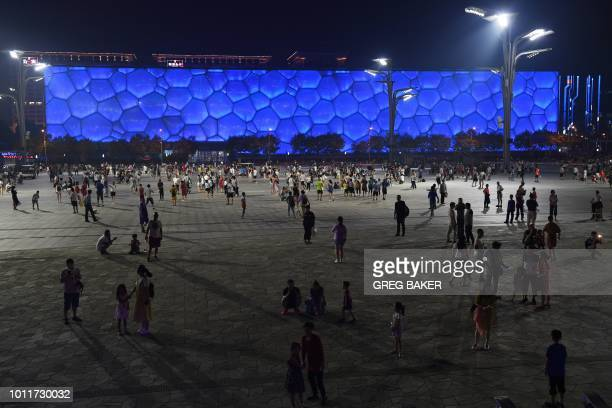 This photo taken on August 1 2018 shows people walking in front of the Water Cube the swimming venue for the 2008 Beijing Olympic Games in Beijing A...