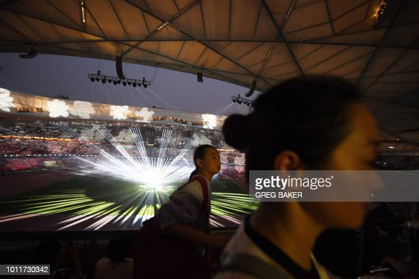 This photo taken on August 1 2018 shows people watching a light show held to mark the 10th anniversary of the 2008 Beijing Olympic Games at the...