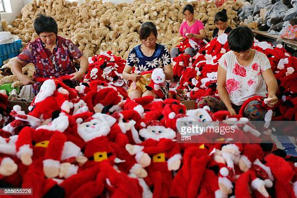 This photo taken on August 10 2016 shows Chinese workers making Santa Claus dolls at a toy factory in Ganyu district in Lianyungang east China's...