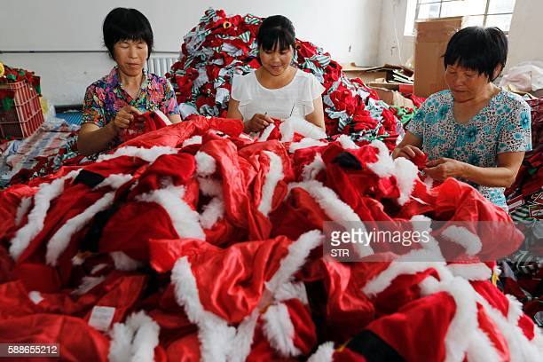 This photo taken on August 10 2016 shows Chinese workers sewing Santa Claus dolls at a toy factory in Ganyu district in Lianyungang east China's...