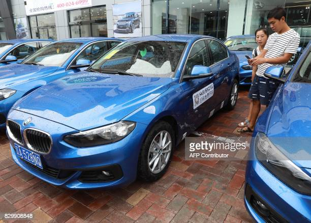 This photo taken on August 10 2017 shows a man scanning a QR code on a BMW 1Series 'sharing car' in Shenyang in China's northeastern Liaoning...