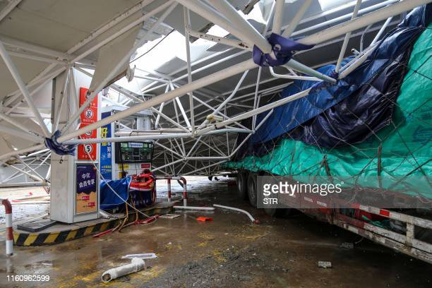 This photo taken on August 10 2019 shows a collapsed roof of a gas station after the area was hit by Typhoon Lekima in Wenling in China's eastern...