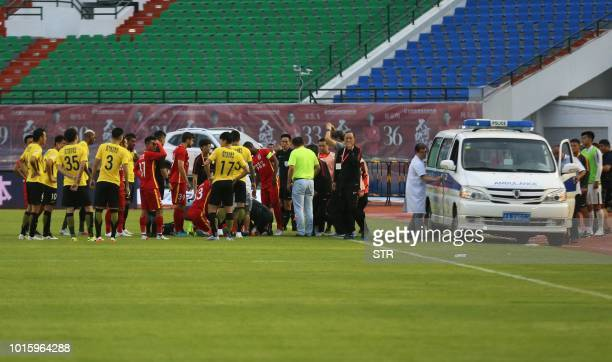 This photo taken on August 11 2018 shows Wang Shouting a player for Chinese club Changchun Yatai receiving medical attention after an injury as...